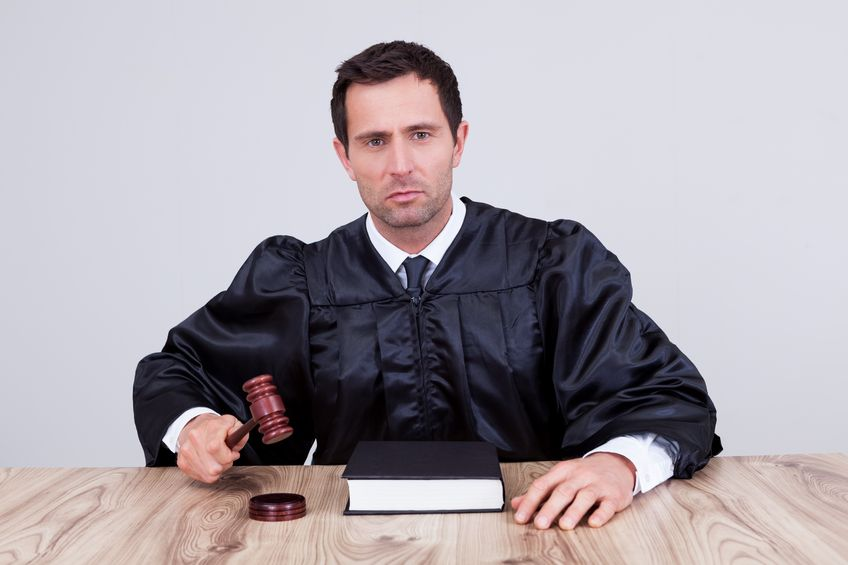 15404299 - male judge in a courtroom striking the gavel